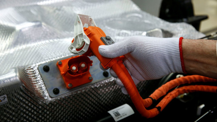 FILE PHOTO: Worker joins battery on VW electronic golf power plant in transparent factory in Dresden