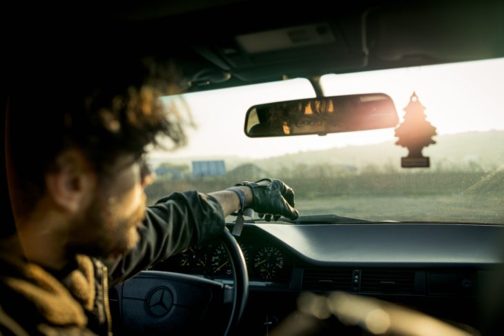 A man in a car, reflected in the rear view at 730x487, on some of the challenges posed by a driver